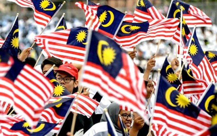 Malaysians waving national flag