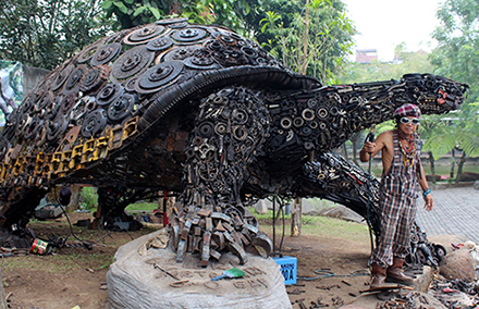 Metal sculptor Ono Gaf with his turtle in Batu, East Java. Photo by Duncan Graham.