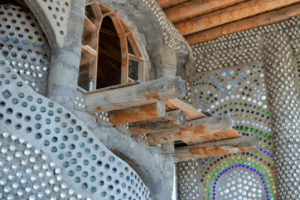 """David Blanchet, an Earthship Academy student, enjoys spending his down time on his own personal balcony. This earthship room he is renting during his stay in Taos is part of a larger infrastructure called """"EVE."""" Photo by Brenna Kelley / NM News Port"""