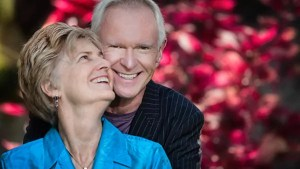 Two older people hold each other and smile in front of a red bush.