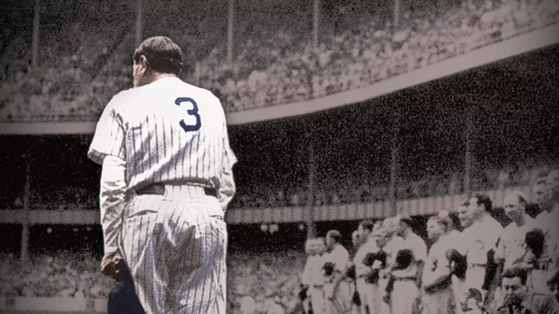 A baseball player stands in the middle of a packed stadium.