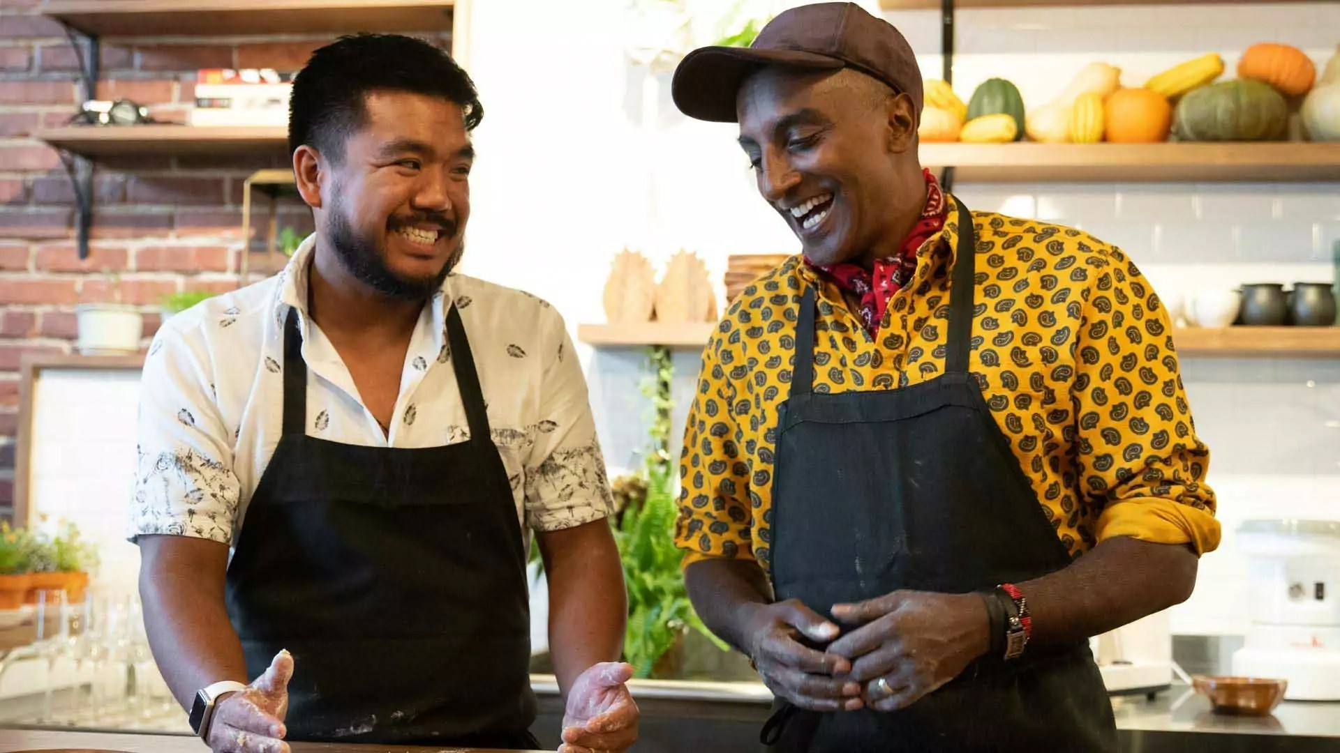 Two people laugh and cook with each other in a kitchen.