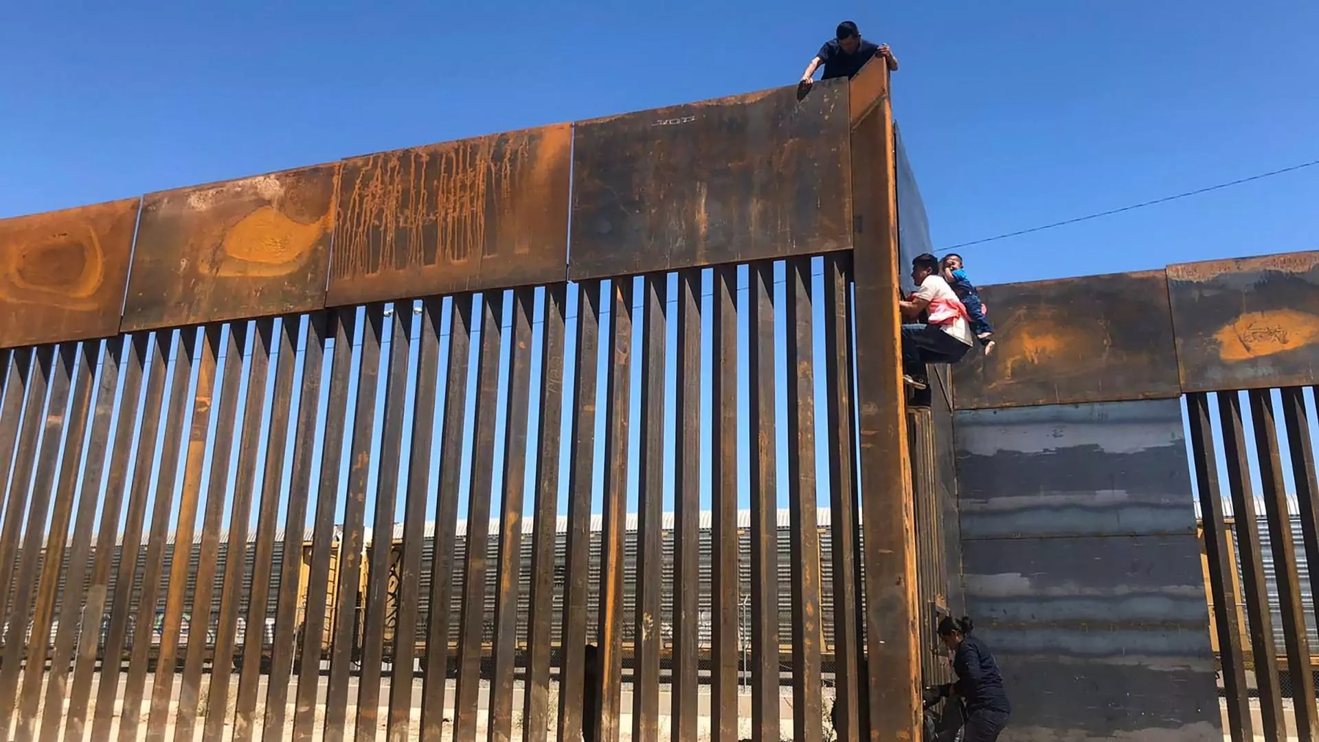 People climb over a border wall in the southern United States.