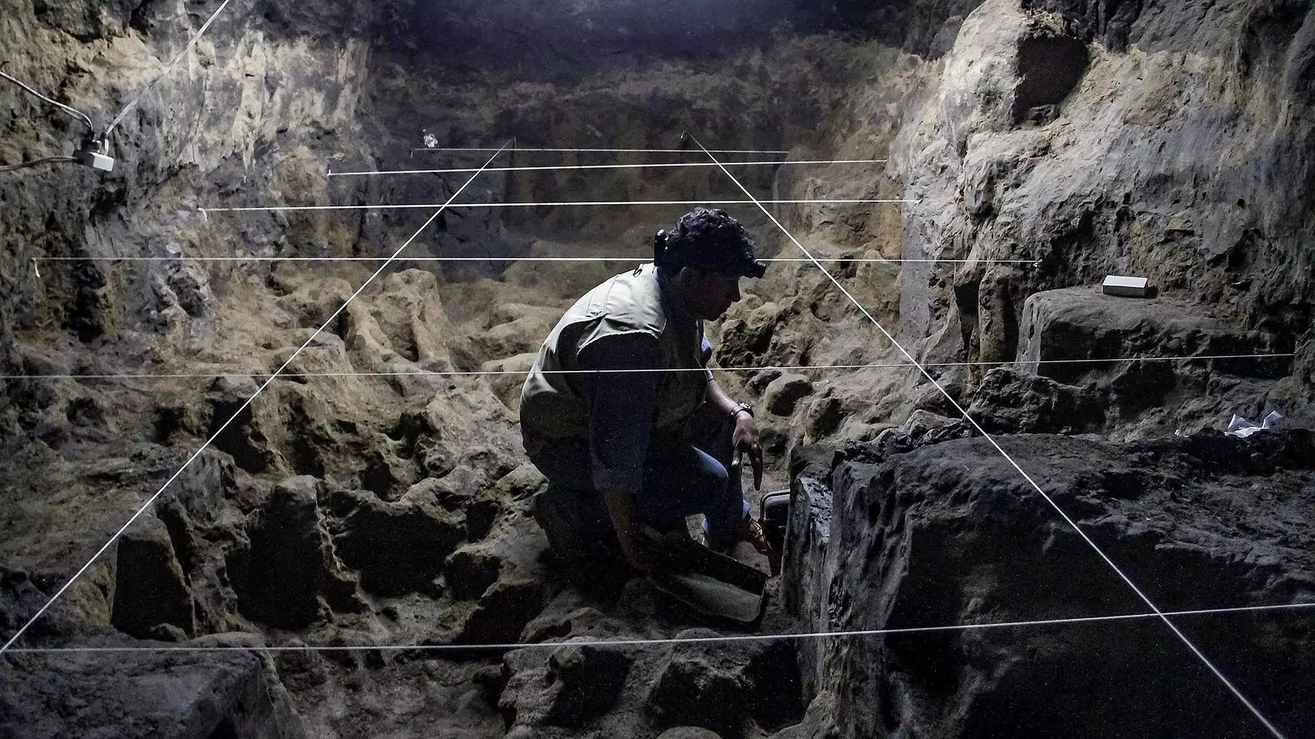 An archaeologist sits and analyzes rocks in a cave.