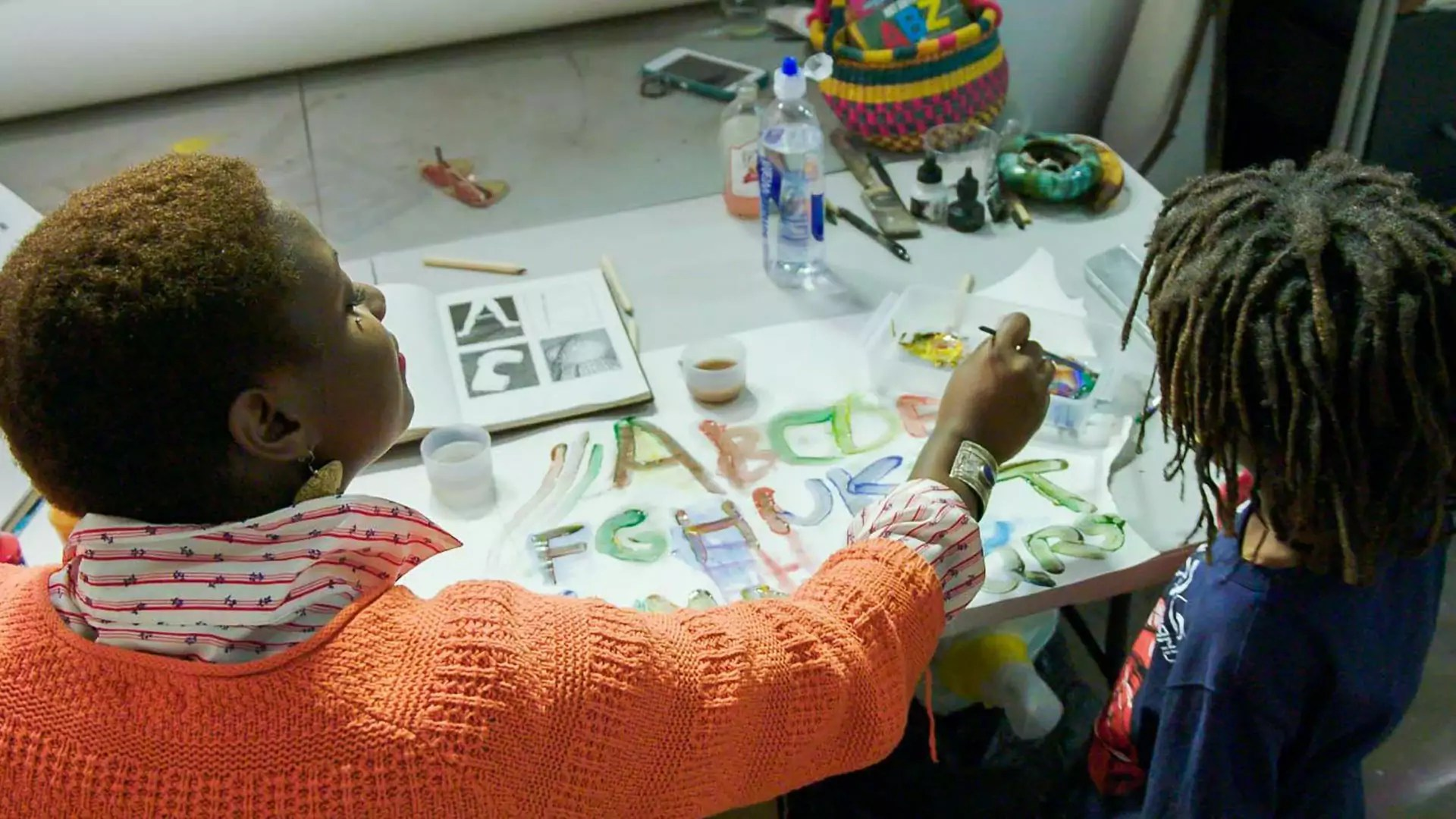 A person dips a brush into paint as a child watches next to them.