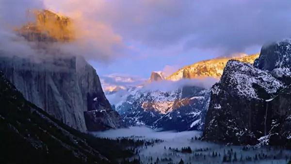 A mountain range covered in snow and fog.