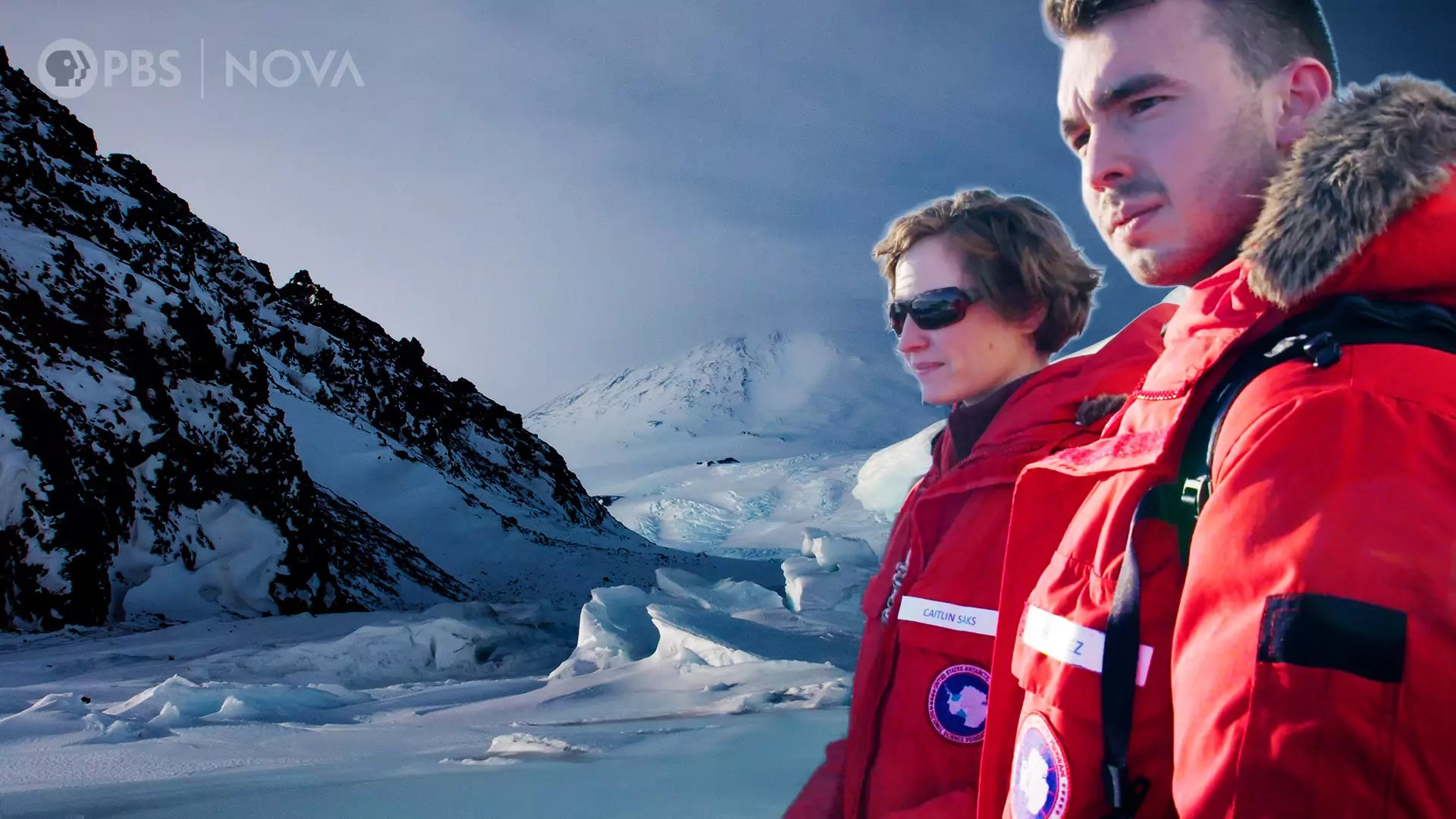 Two people in large coats, with the landscape of Antarctica in the background.