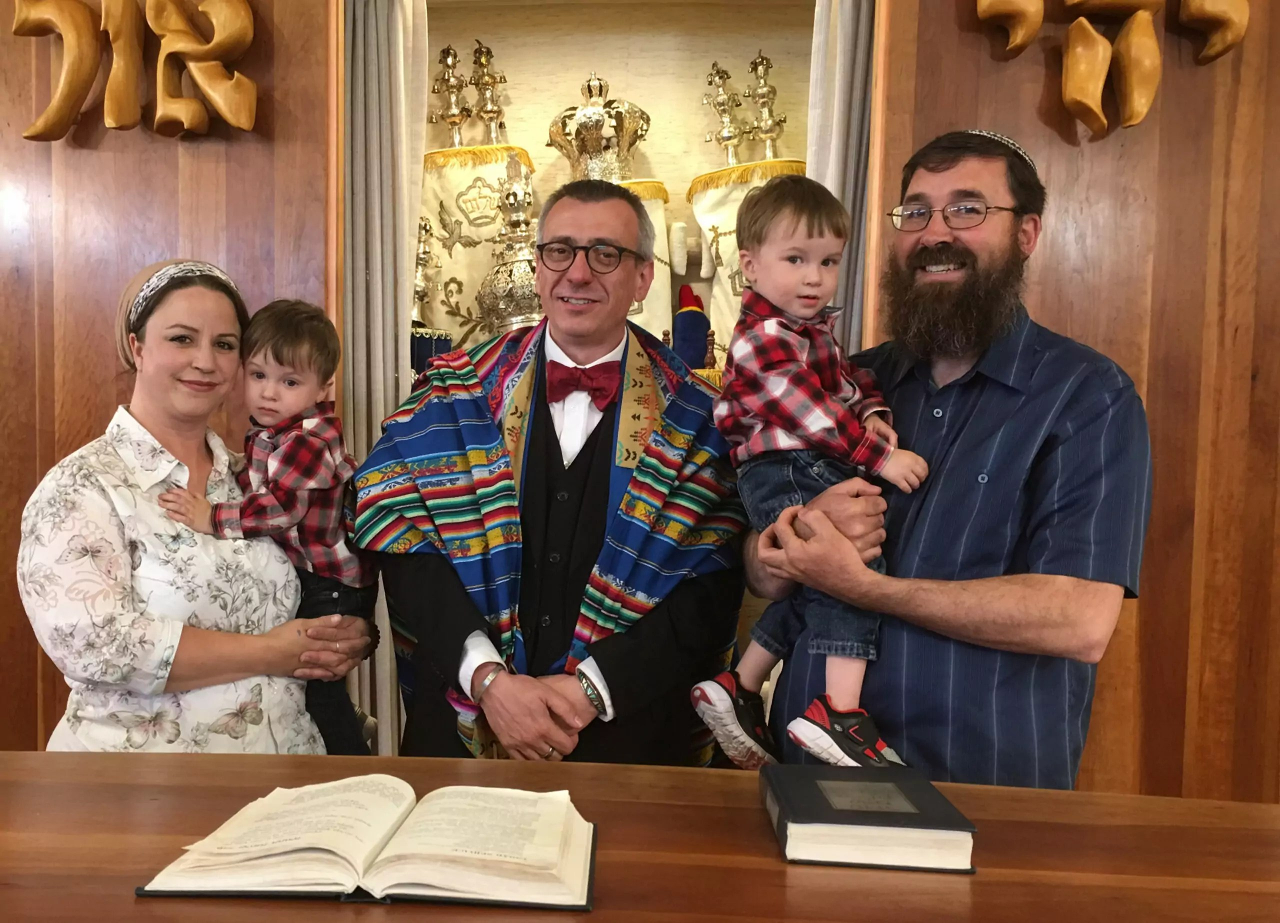 Two people hold their children while smiling, while a rabbi stands in the middle.