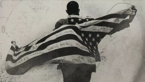 A person, with their back to camera, drapes an American flag over their back, with the flag marked up with several names.