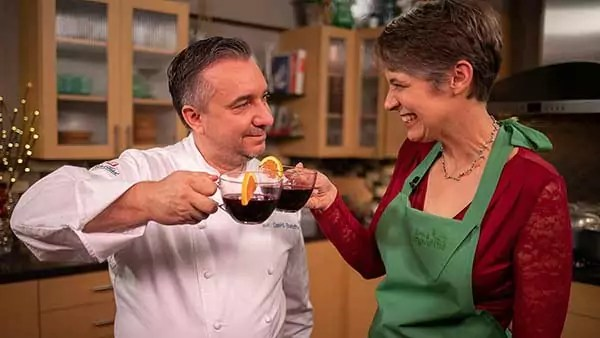 Two people clink glasses of sangria with orange slices, smiling.
