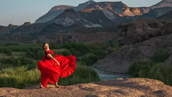 A dancer wearing a puffy dress stands in front of a mountain.