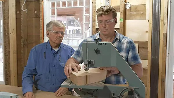 Two men wear safety glasses while one of them cuts some wood.