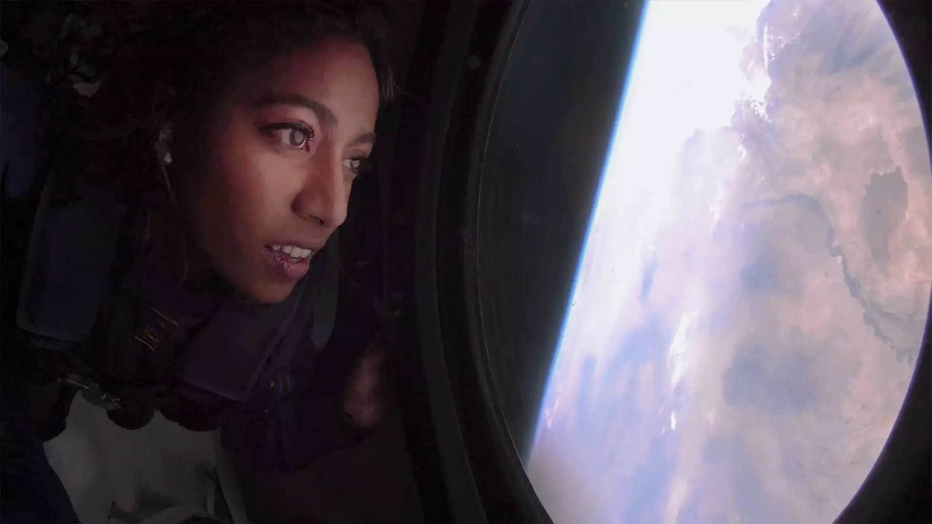 A woman looks out a window at Earth from the Virgin Galactic