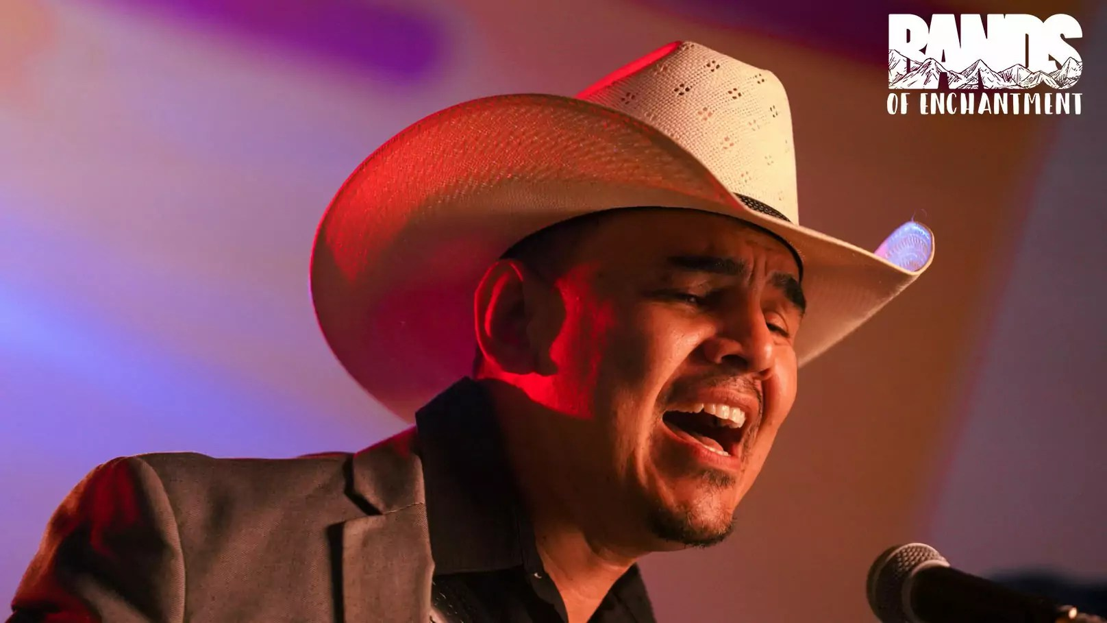 A man with a cowboy hat sings into a microphone