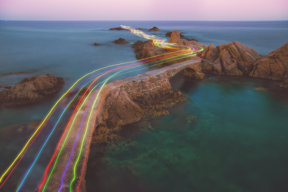 Long exposure of a colorful rainbow of light traces in a beautiful curved path between the rocks over the Mediterranean Sea in the Costa Brava shoreline on sunset.