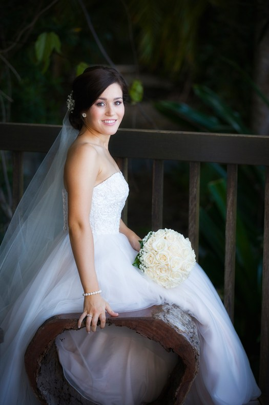 Half length semi formal bridal portrat of bride seated in front of rainforest background. Wedding Photos in Palm Cove by Excitations, Mildura photographers.