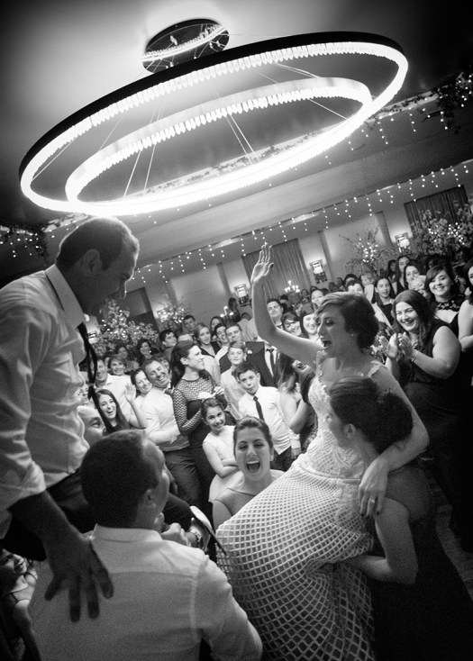 Black and white action wedding photo of bride and groom on shoulders of guest as they party the night away.