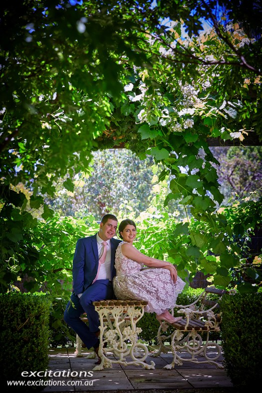 Engaged couple under a pergola covered in lush green vines. Location photography by excitations.