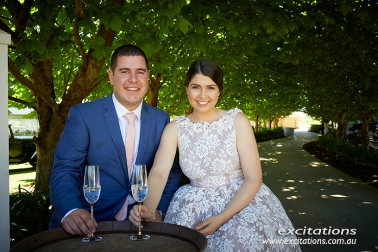 Engagement couple seated in behind a wine barrel bar under a long avenue of London Plane Trees. Engagement photography by Excitations.