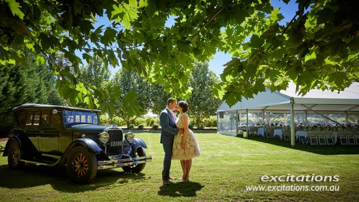 Engaged couple kiss beside a vintage car with venue marquee in background. Photo by Mildurra photographer Excitations.