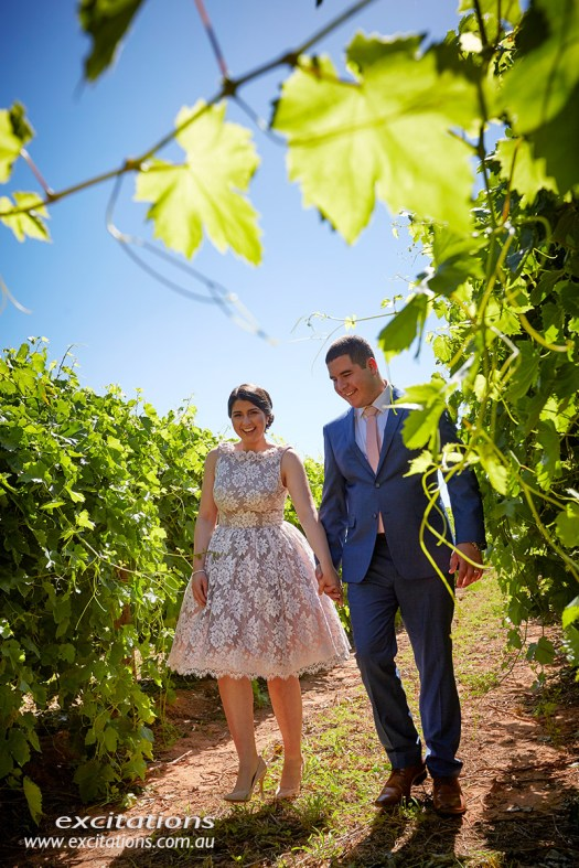 Couple walking in vineyard. Engagement photography Mildura by Excitations.