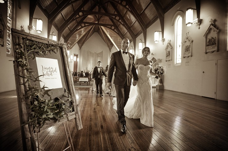 toned monochrom photo of newly married couple leaving church. Excitations, Mildura