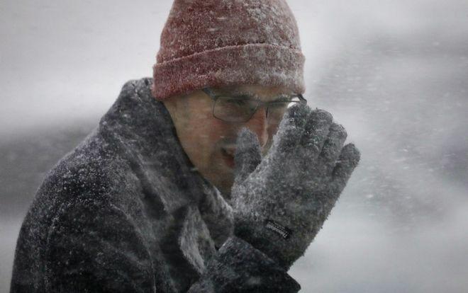 Άνδρας βάζει το χέρι με το γάντι προκειμένου να προστατευτεί από τις ριπές του ανέμου