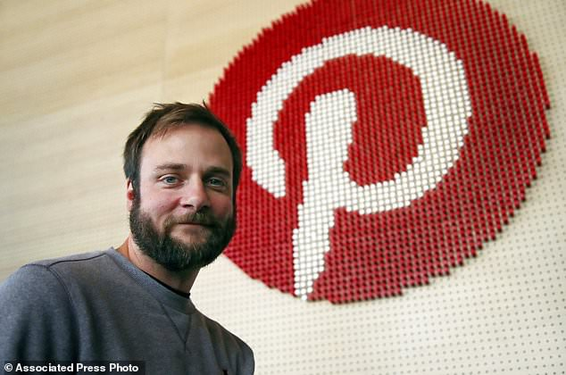 In this Thursday, Oct. 11, 2018, photo Evan Sharp, Pinterest co-founder and chief product officer, poses for a photo stands beside a wall of pegs symbolizing the company logo at Pinterest headquarters in San Francisco. 'Social media is about sharing what you are doing with other people,' said Sharp. 'Pinterest isn't about sharing. It's mostly about yourself, your dreams, your ideas you want for your future.'