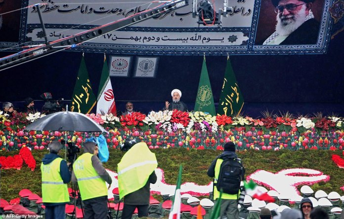 Iranian President Hassan Rouhani speaks to crowds of thousands on a flower-covered stage during a ceremony on Monday
