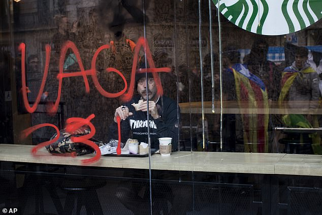 "A man eats inside a coffeeshop with a glass painted with a graffiti reading in Catalan: ""strike"""