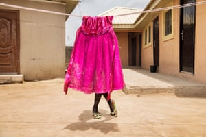 A child plays with the laundry drying in the sun in Gwagwalada