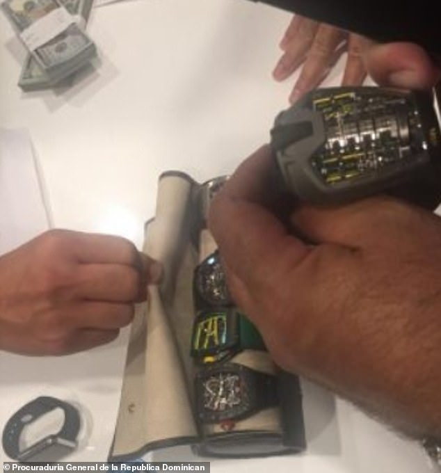 Investigators inspect some of the watches that were seized during Sunday's raid