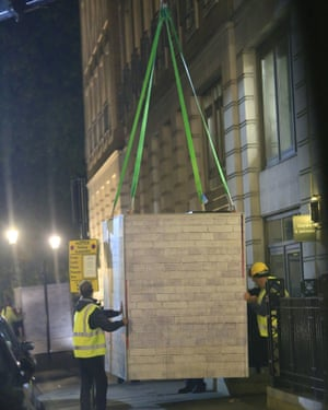 Greenpeace activists position one of the heavy containers outside BP headquarters