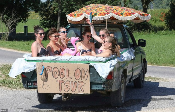 Six young women cool themselves in water in a pick-up truck , that they sealed with a plastic sheet in Unlingen, southern Germany