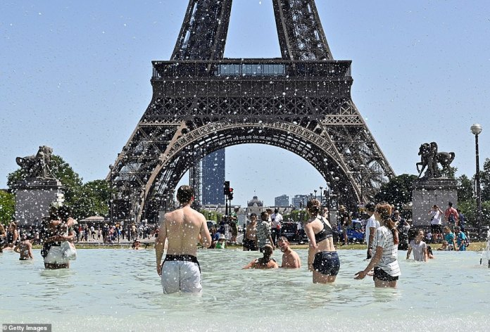 People cool down in the fountains of Trocadero near the Eiffel Tower as France continues to swelter in the record-breaking heatwave