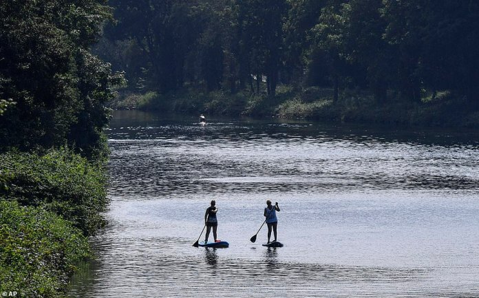 Two women paddle on their stand-up boards during the hot summer weather on the Rhine-Herne canal at the Ruhr valley in Gelsenkirchen, Germany