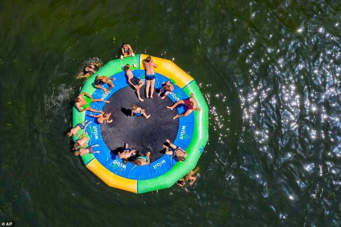 People enjoy the hot summer weather on a water trampoline at a lake in Moers, Germany, today, amid a heatwave across Europe