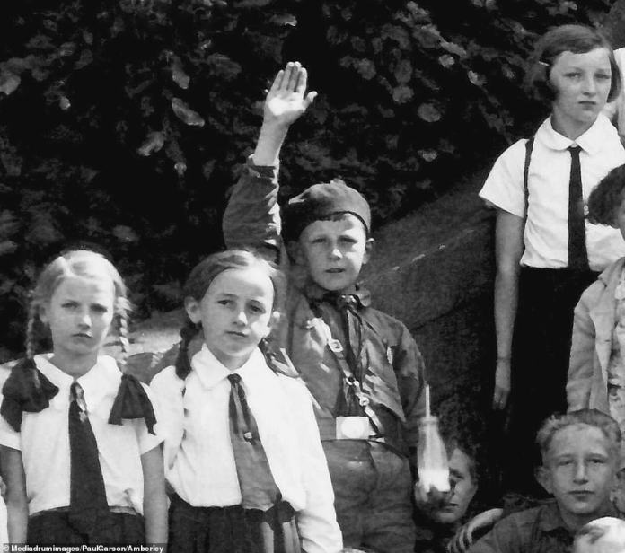 Young blood: A child holds a bottle of milk in one hand - and makes a Nazi salute with the other. Seemingly a member of the Hitler Youth, he is flanked by other youngsters in similar uniforms. From 1936, membership of the Hitler Youth or League of German Girls (BDM) was compulsory for children aged between 10 and 18. By the end of the war, the Nazis' military situation was so dire that Hitler sent child soldiers to their deaths in a last-ditch effort to save his crumbling regime