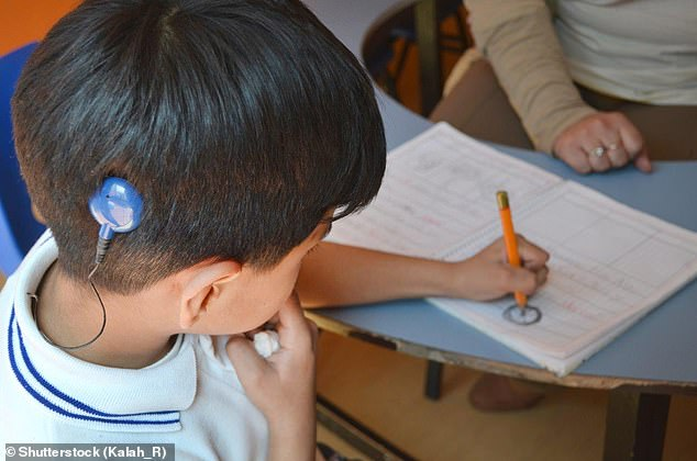 Around 11million people in the UK – one in six – are deaf or have a hearing loss and about 1,200 are fitted with cochlear implants each year (stock image of a boy with a cochlear implant)