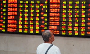 An investor watches an electronic ticker board at a stock market in Nanjing, China