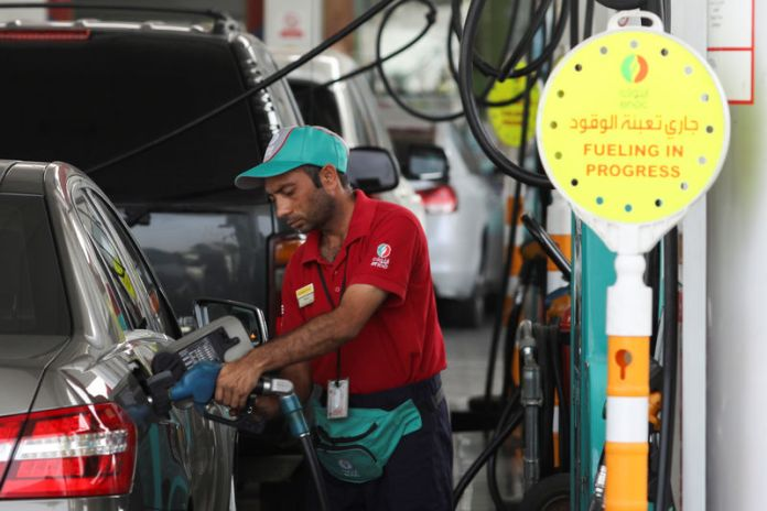 © Reuters. A worker fills a vehcile with petrol at a gas station in Dubai