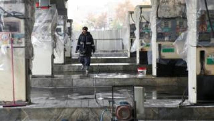 A man walks near the remains of petrol pump stands, during protests against increased fuel prices, in Tehran, Iran, 20 November, 2019.