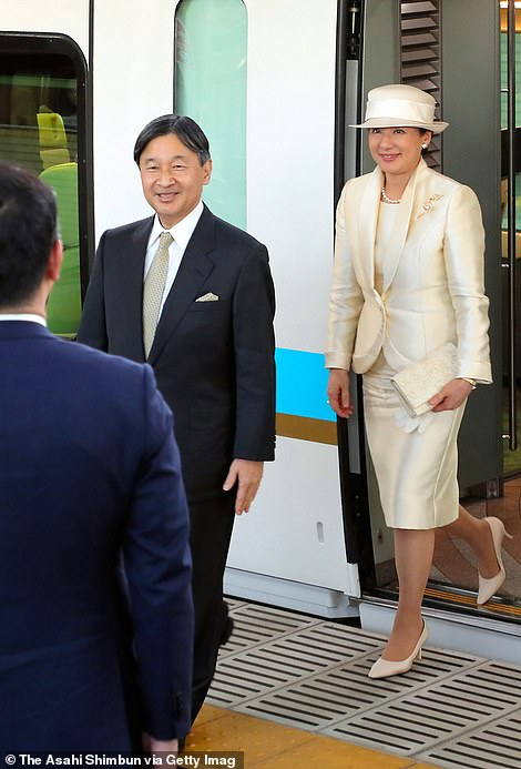 The pair arrive attheKintetsu Ujiyamada station on their way to the Ise Shrine, the emperors wears an all cream silk suit with hat while the emperor wears a classic black suit