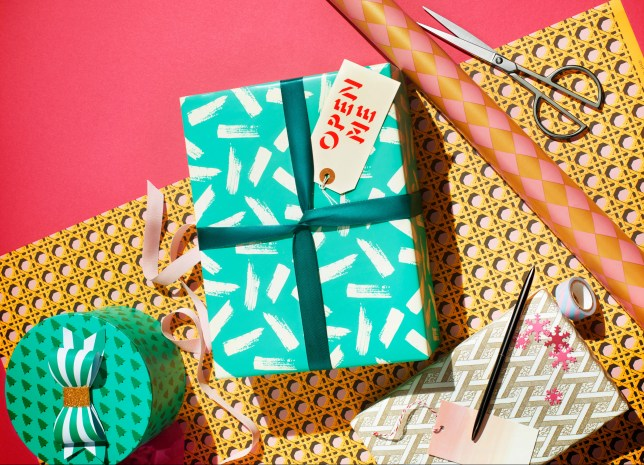 Neatly wrapped box with wrapping paper, scissors, tape and pen.