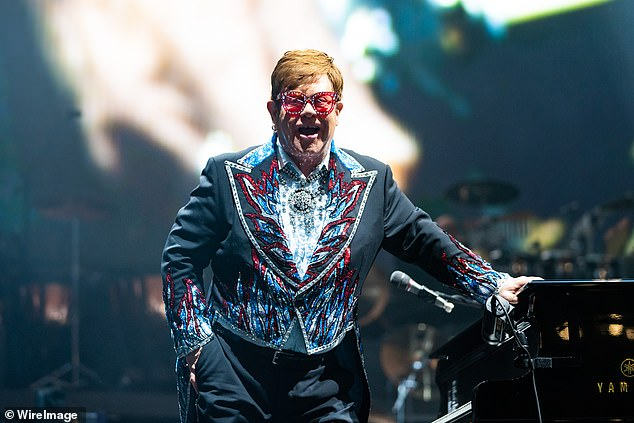 Shiny!Elton wore his trademark flamboyant sunglasses with red lenses, bedazzled with rhinestones