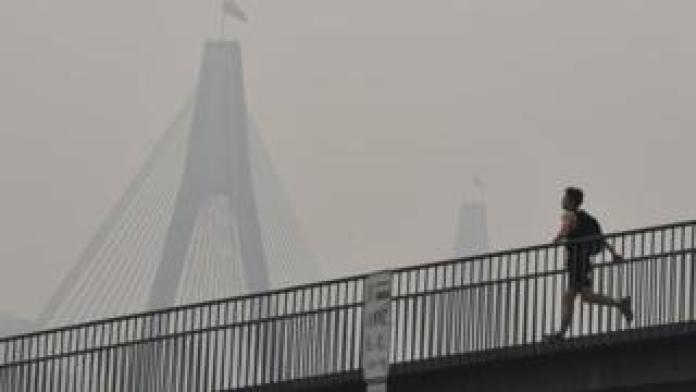 A man runs over a bridge during a smoky haze in Sydney on Tuesday
