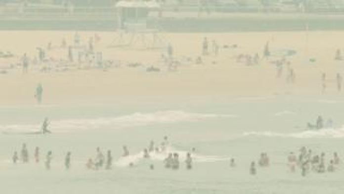 Beachgoers on Bondi Beach amid a heavy smoke haze,