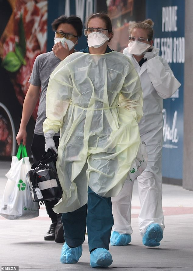 Paramedics wearing hazmat suits arrived in Broadbeach, Australia, to reports of a suspected coronavirus case on Tuesday – they are pictured escorting the male patient out to an ambulance
