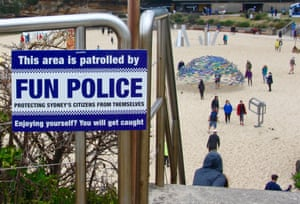 "A ""fun police"" sign installed at a beach."