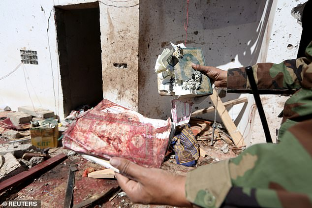 Saudi Arabia's foreign ministry today said of Saturday's attack that 'such heinous, terrorist crimes deliberately undermine the path to a political solution' in the Yemeni conflict, according the kingdom's official news agency (pictured: a destroyed copy of the Quran is held by a soldier)